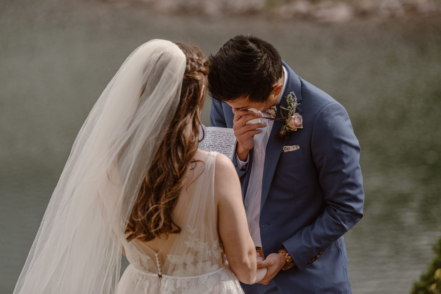 Groom wipes off tear while bride reads vows during their wedding ceremony.