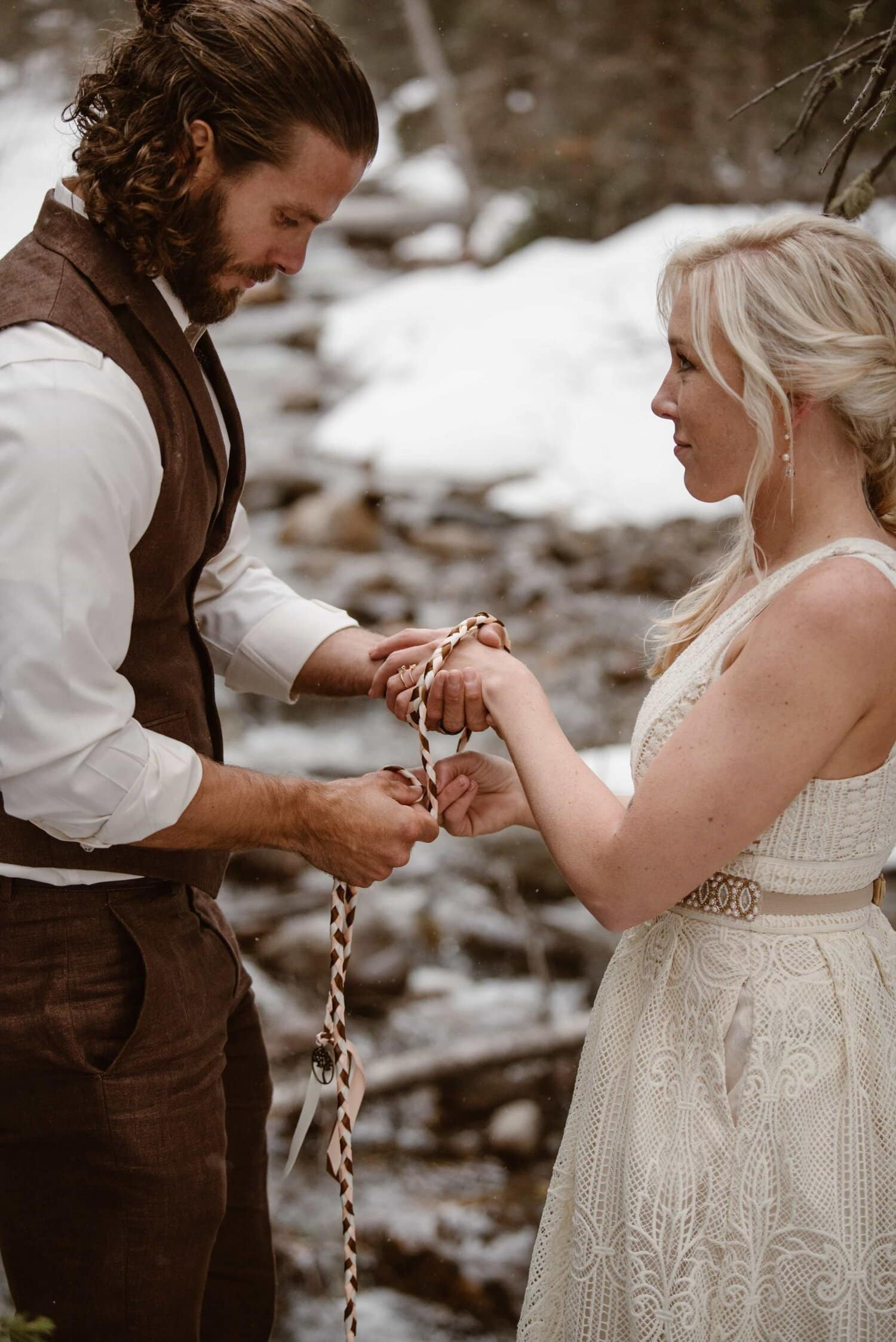 Groom ties rope around bride's hand during their wedding ceremony.