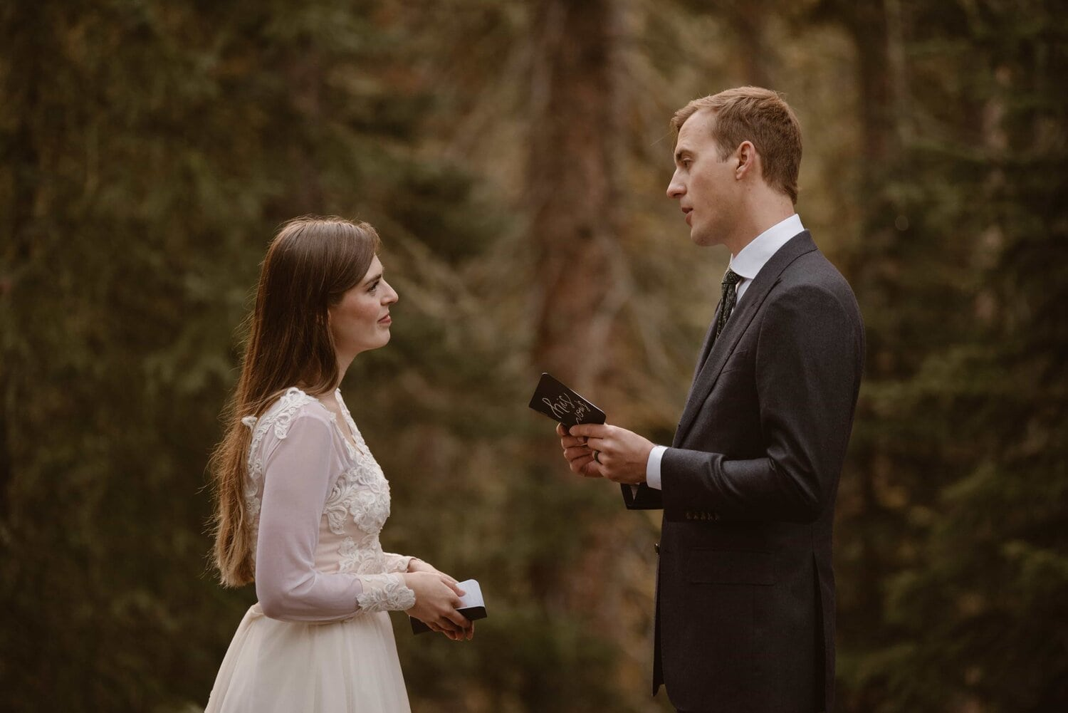 Bride and groom exchange vows in a forest during their wedding ceremony.