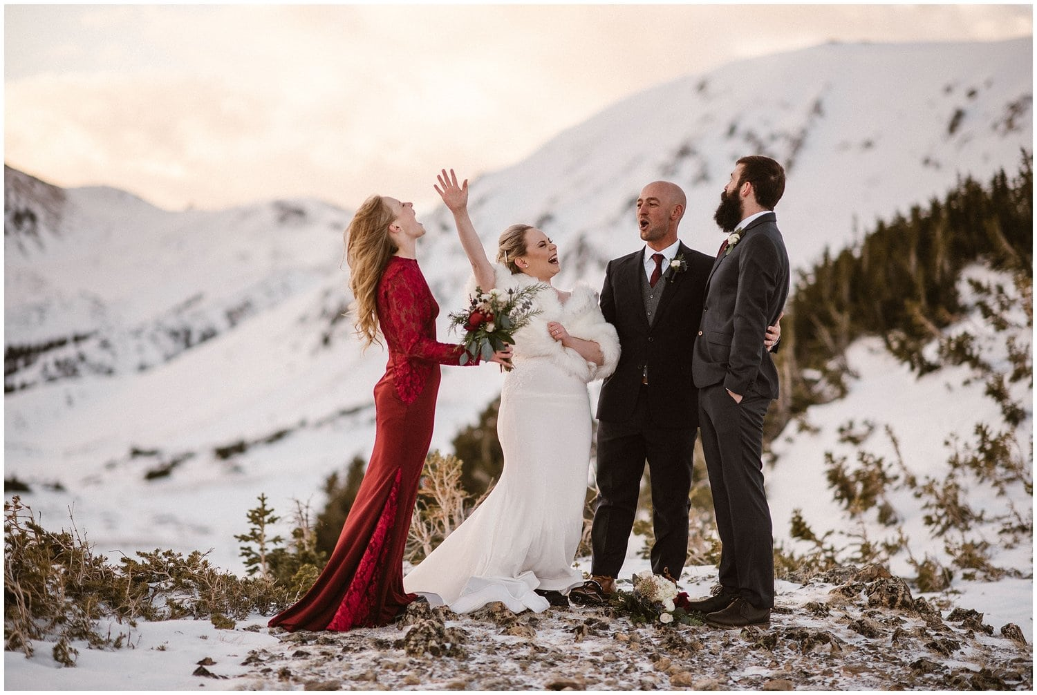 A bride and groom yell in the mountains while a woman and man stand by their side in the mountains.