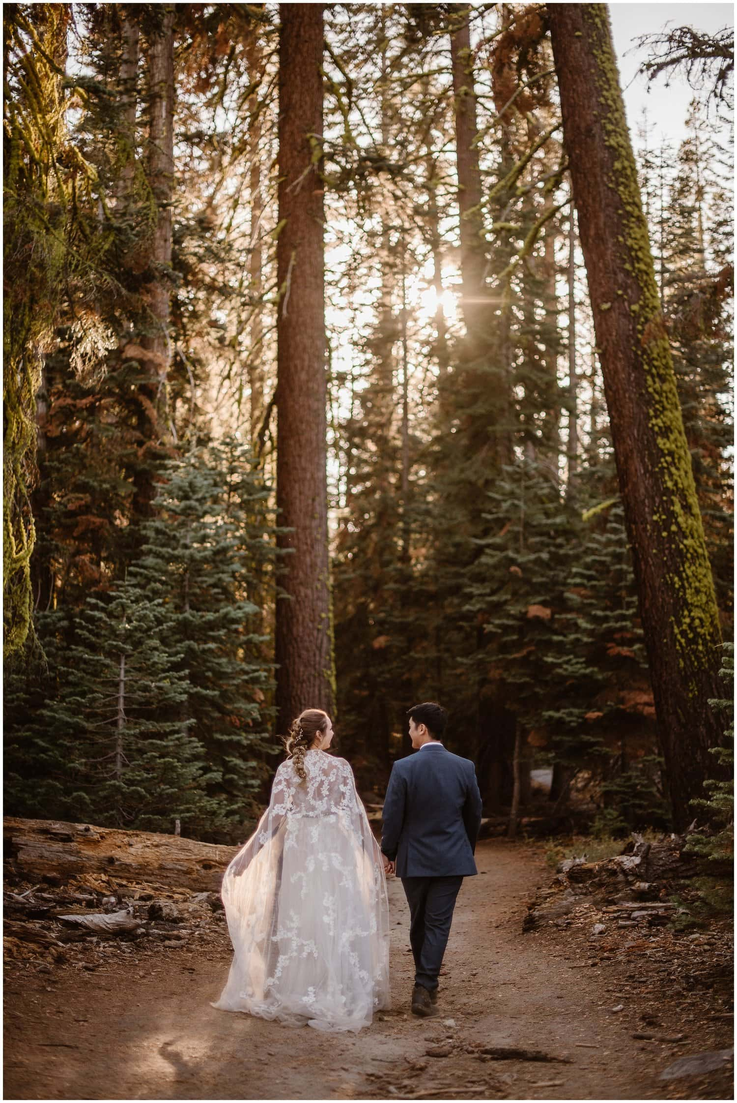 Bride and groom walk hand in hand in a forest in California on their wedding day.