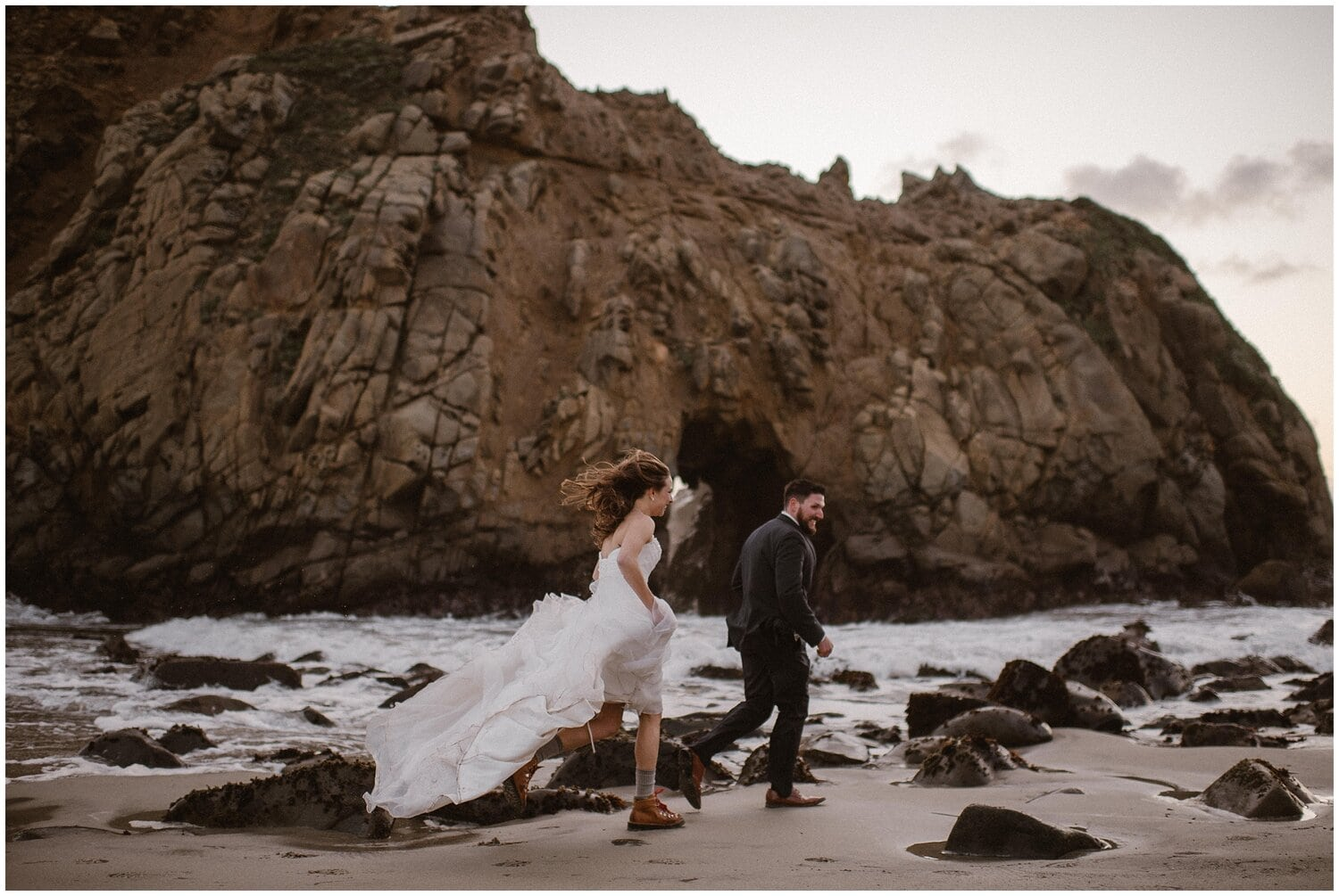 A bride in a white, flowy elopement dress runs across the beach with her groom.