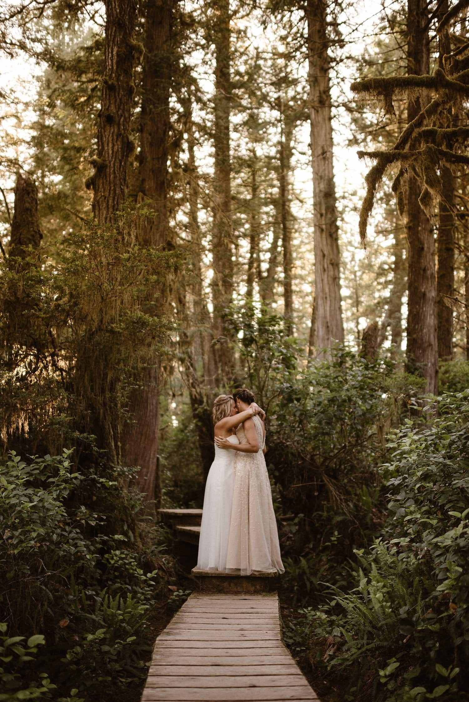 Two brides embrace in a forest.