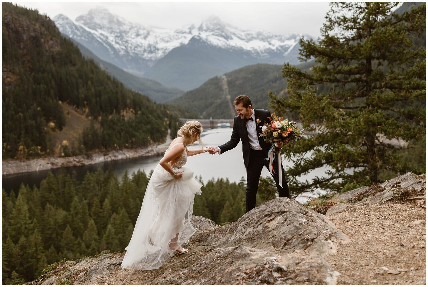 Groom helps bride climb over a rock on their wedding day.