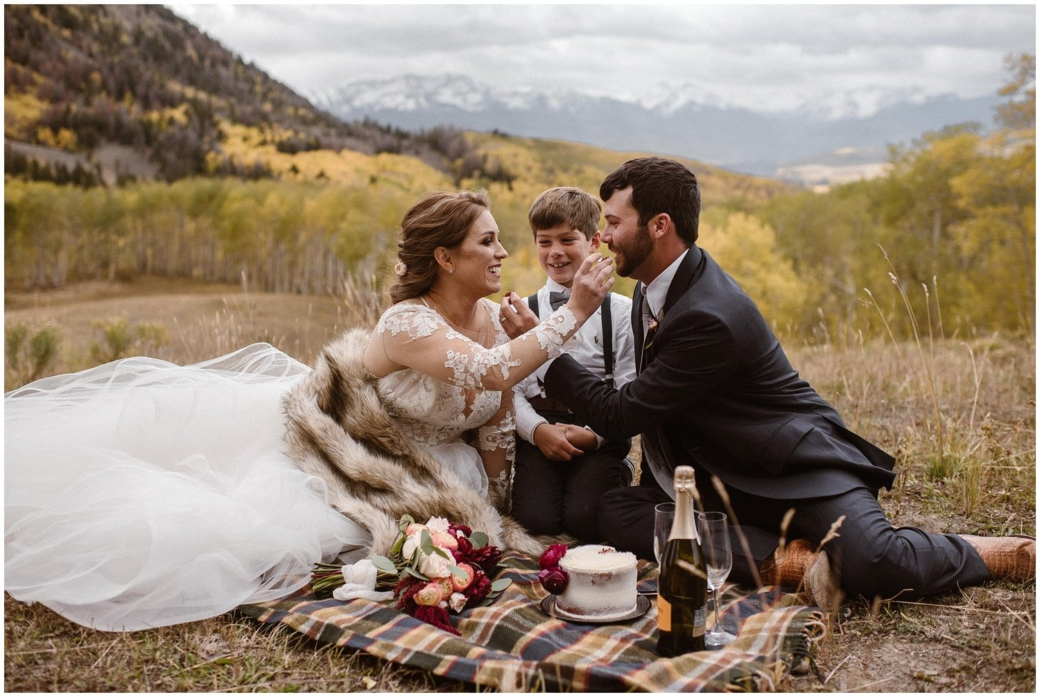 Bride and groom have a picnic with their son on their wedding day.