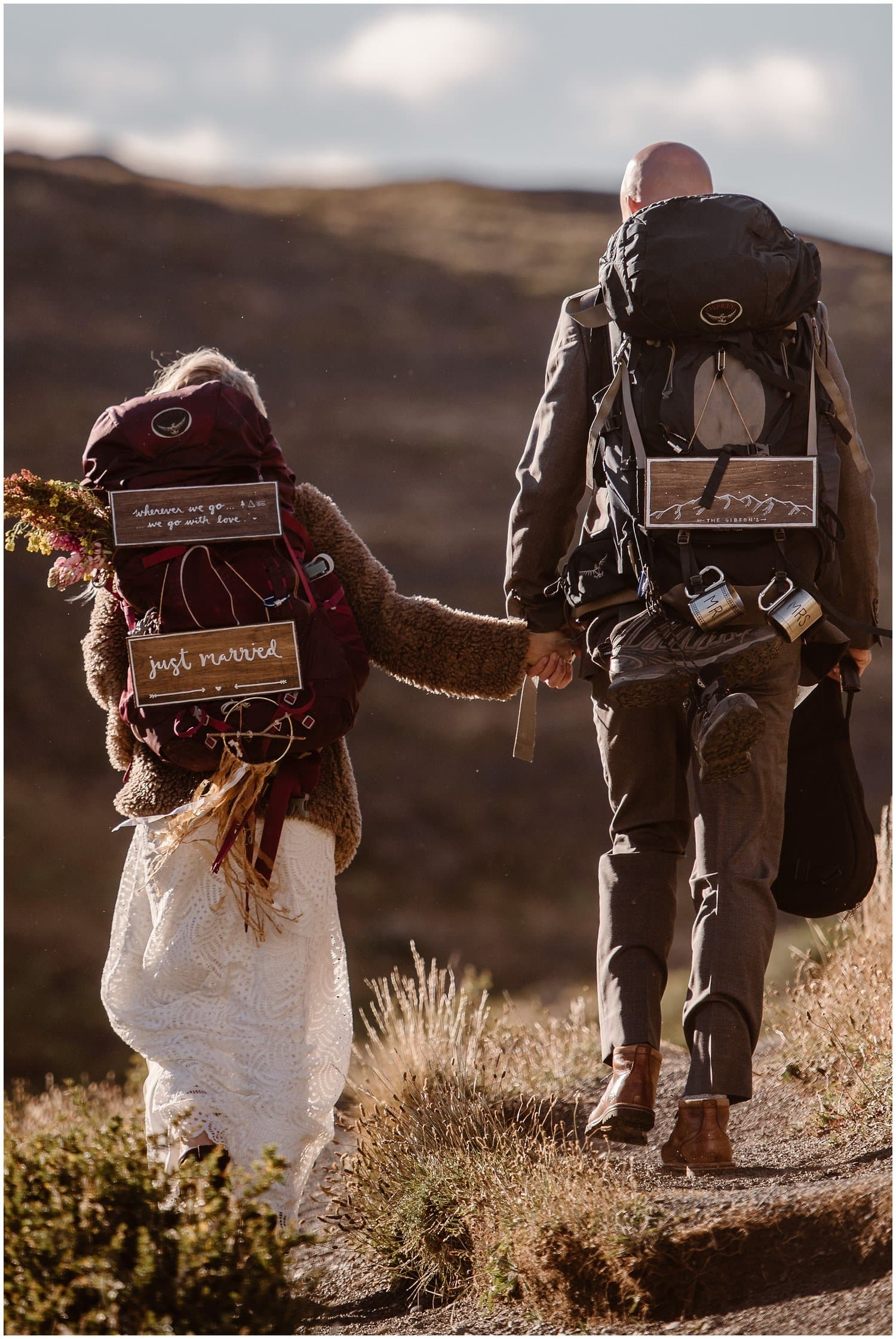 Bride and groom walk hand in hand in the mountains. Both of them are wearing backpacks with wooden married signs attached to them.