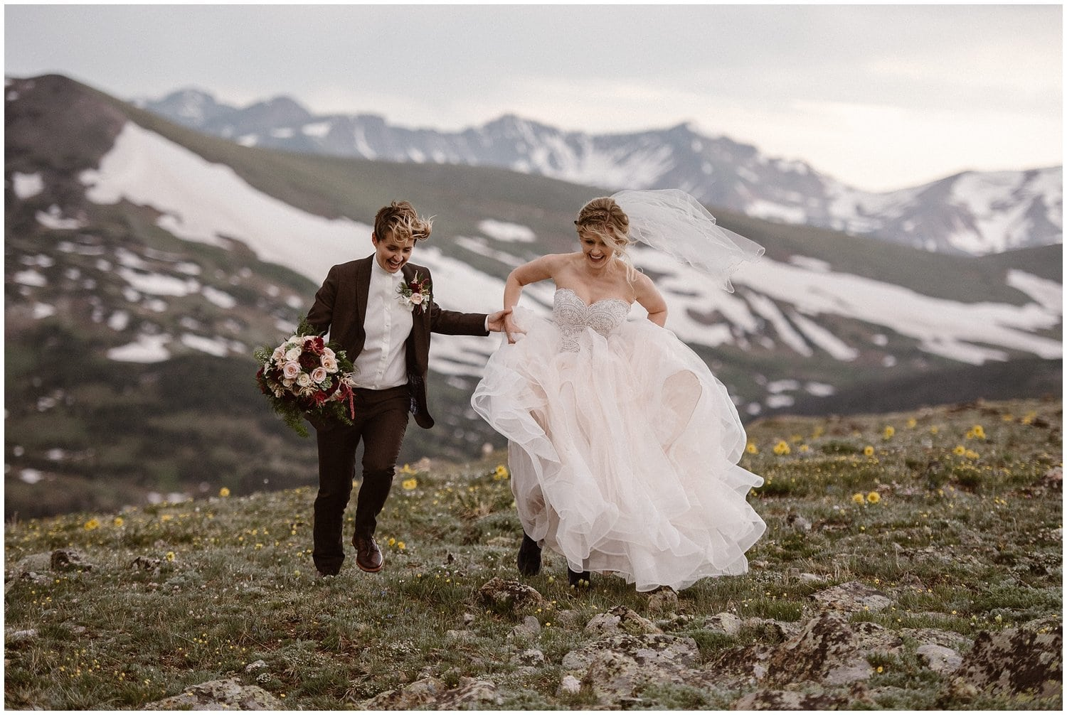 A couple runs hand in hand in the mountains on their wedding day.