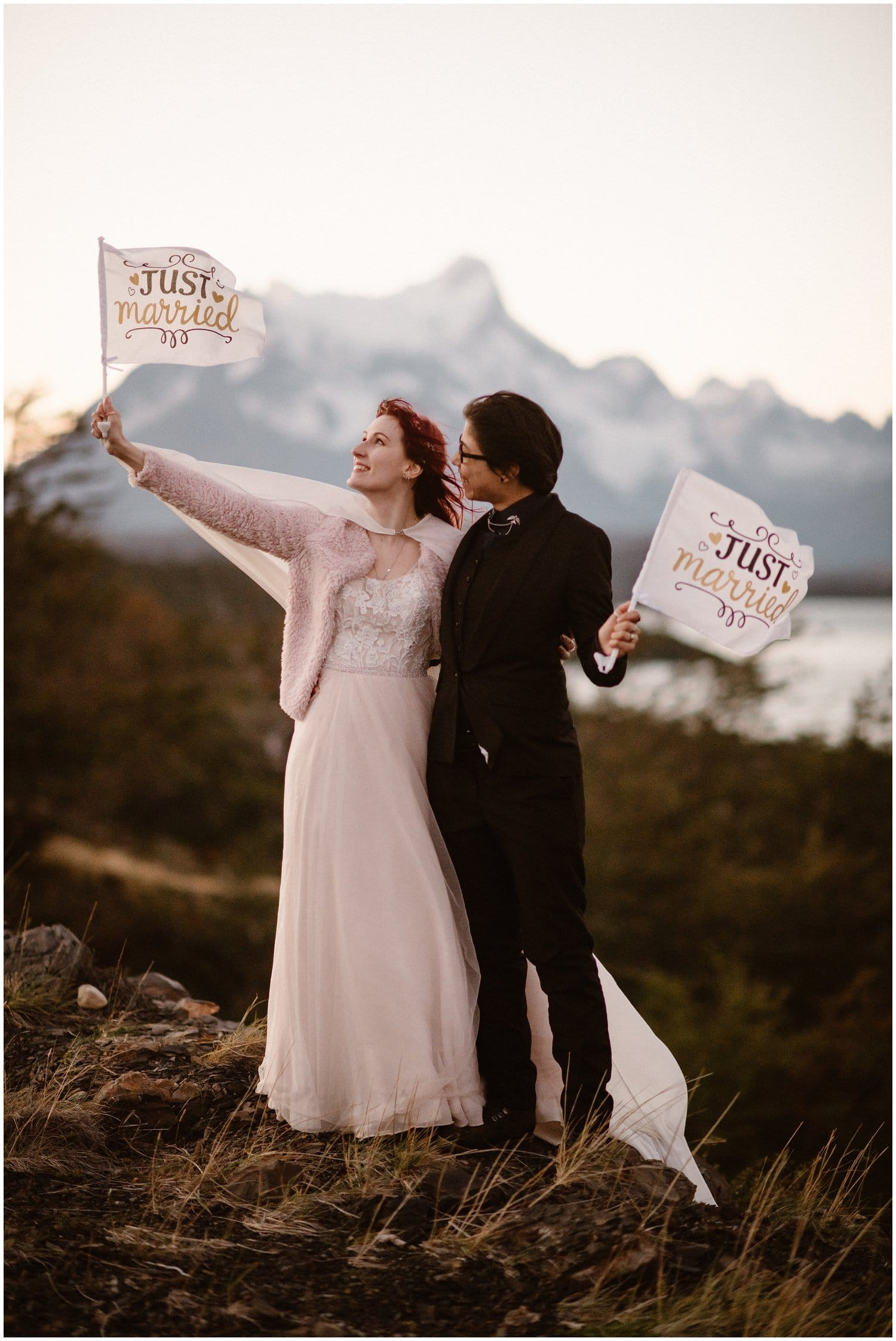 "A couple hold ""Just Married"" signs in the mountains on their wedding day."