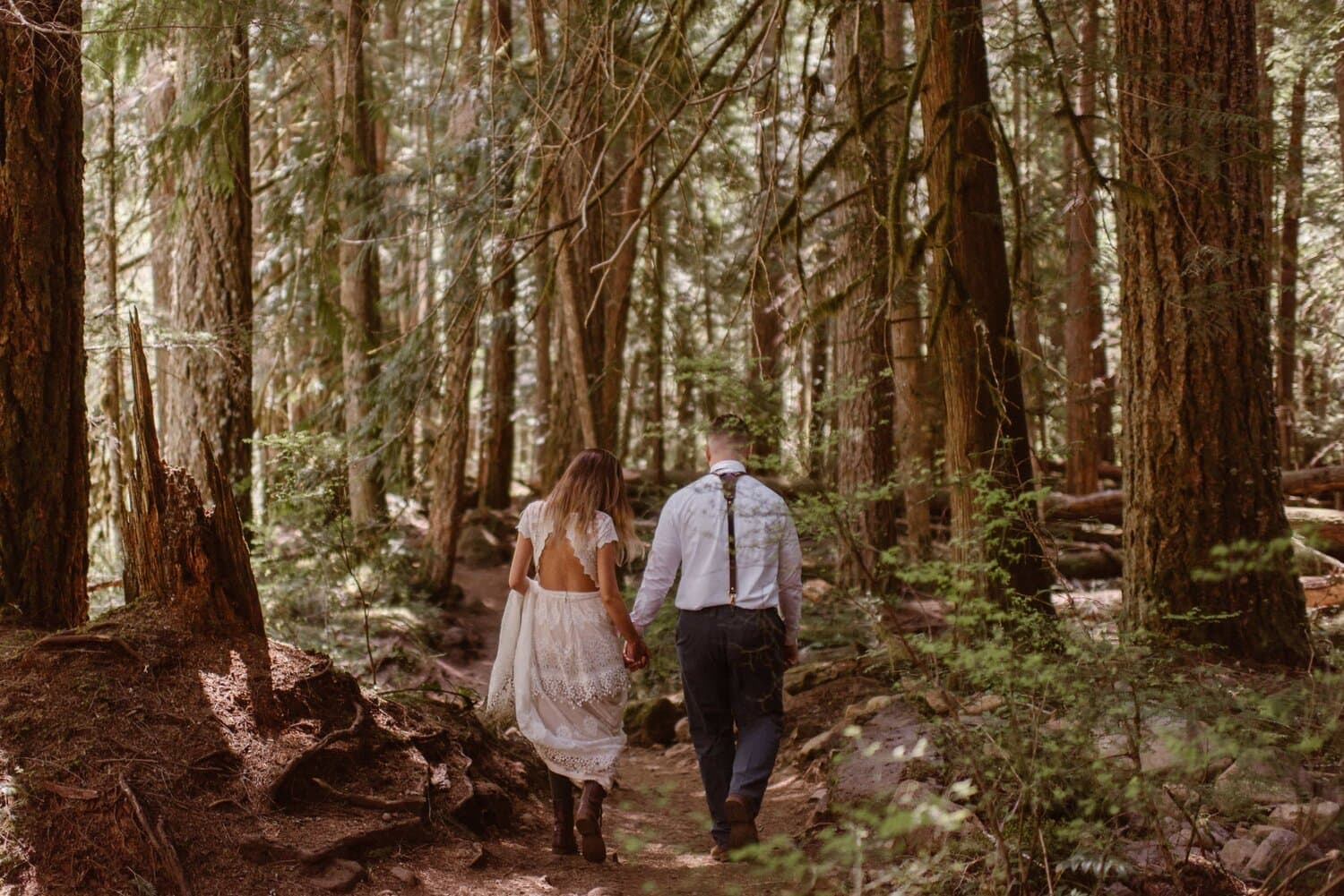 A bride and groom hold hands while walking through a forest.