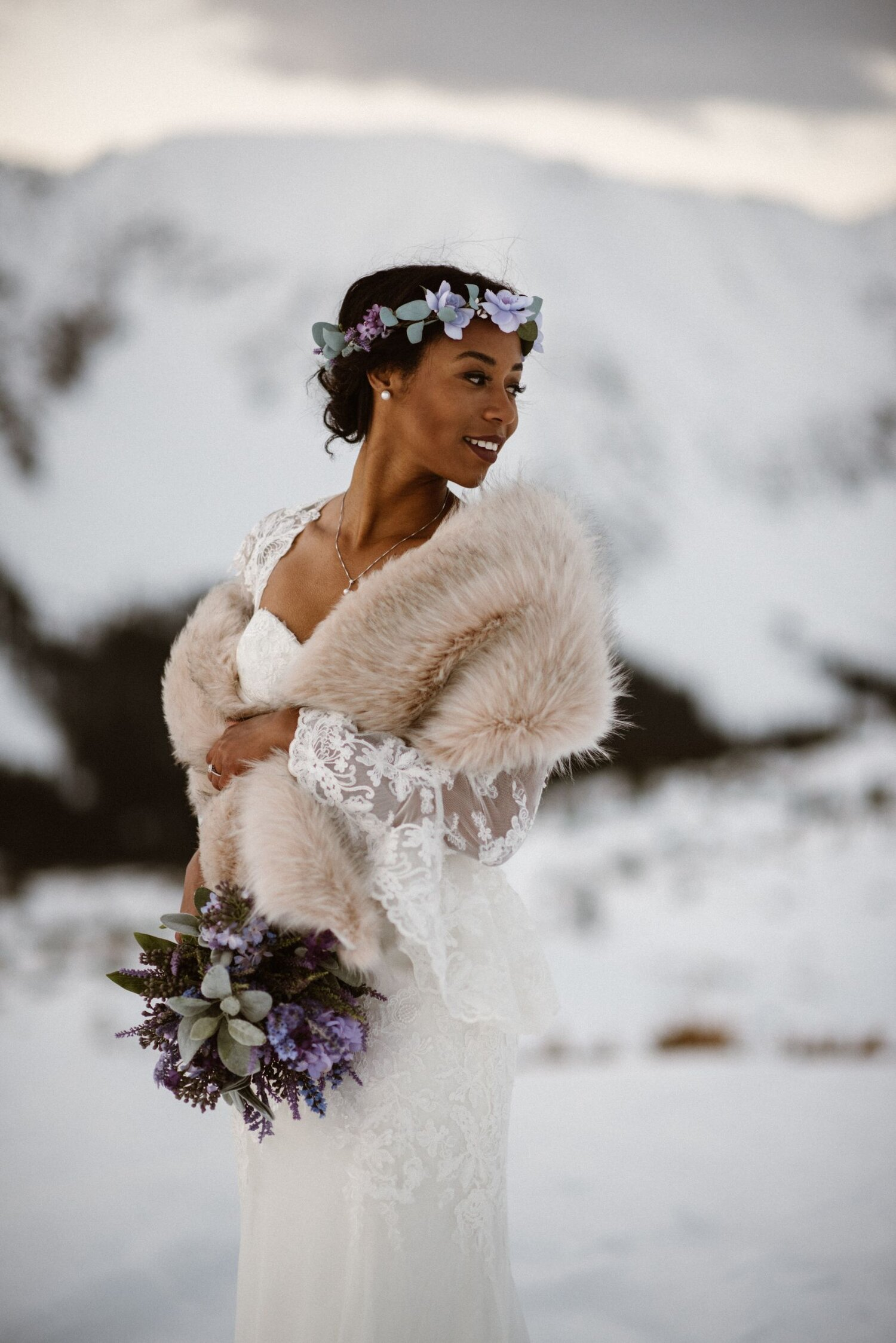 Bride dressed in a white elopement dress  is wearing a fur shawl and has a purple flower crown and bouquet.