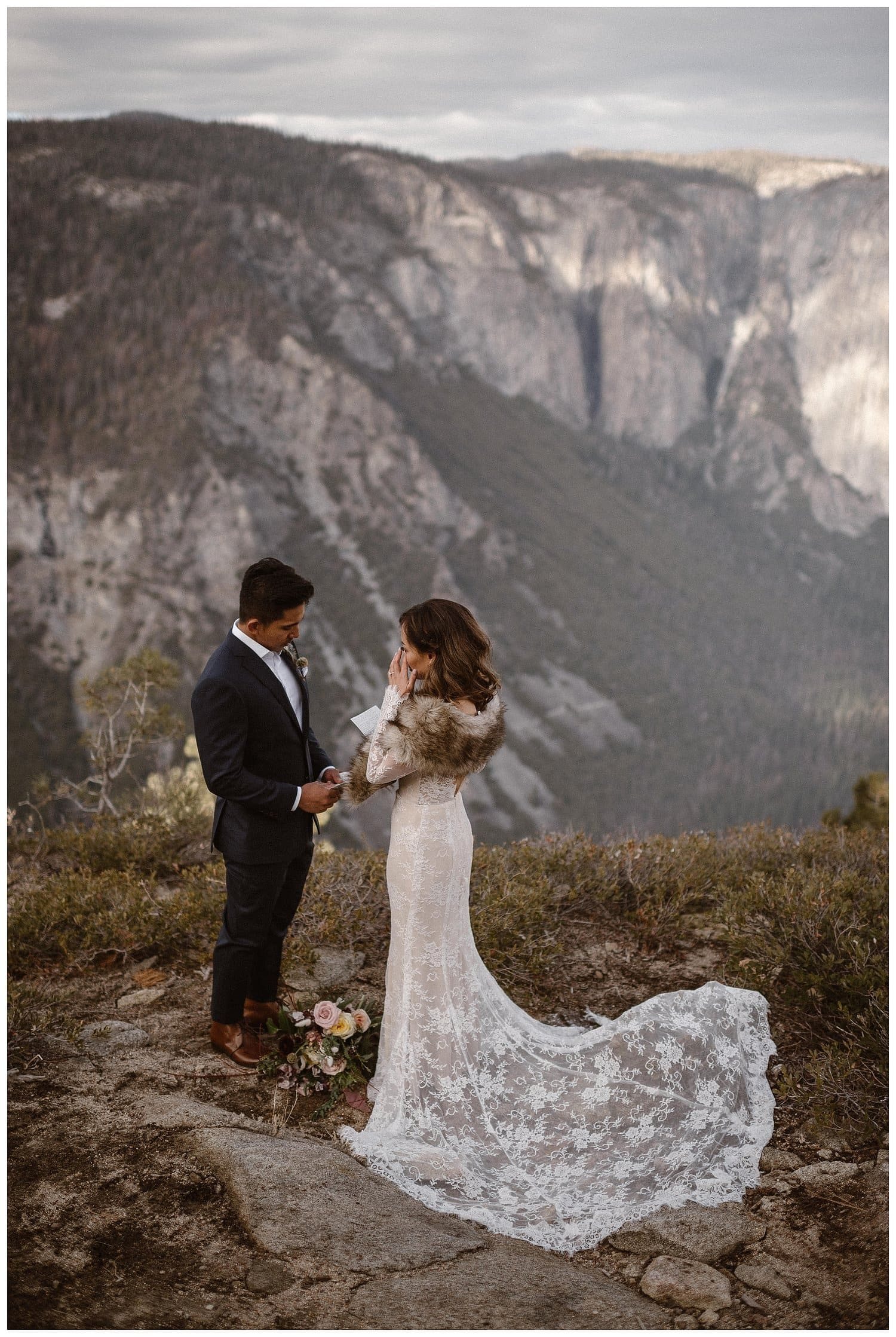 Bride wipes tear off her face while reading vows to the groom in Yosemite National Park on their wedding day.
