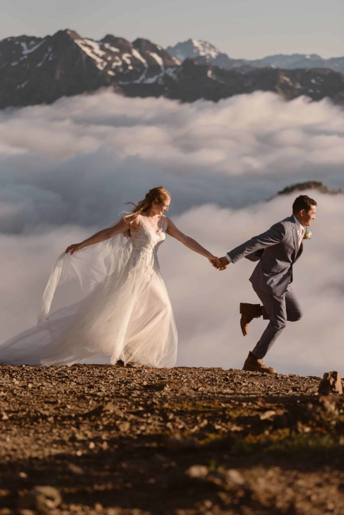 A bride and groom run hand in hand in the mountains with a cloud inversion in the background.
