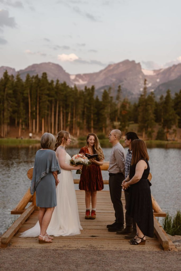Bride and groom have their wedding ceremony with family and friends near the lake.