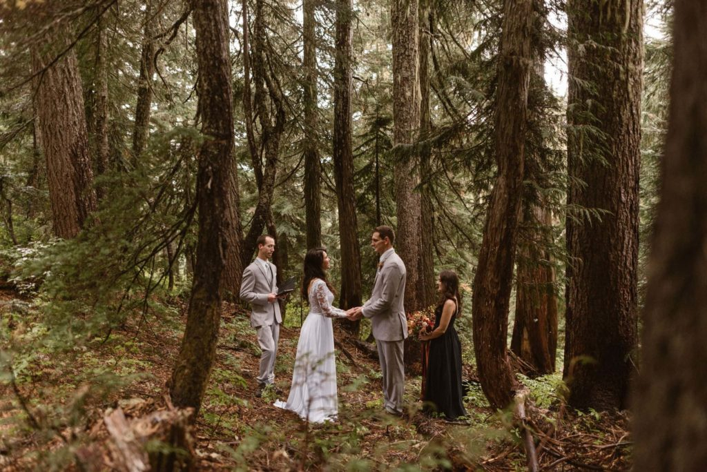 Bride and groom have their wedding ceremony in the forest with two witnesses standing by their sides.