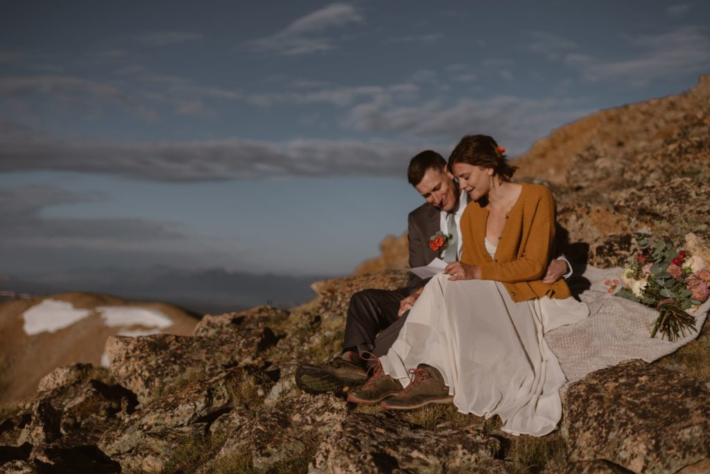 Bride and groom read letters from family and friends on top of the mountains.