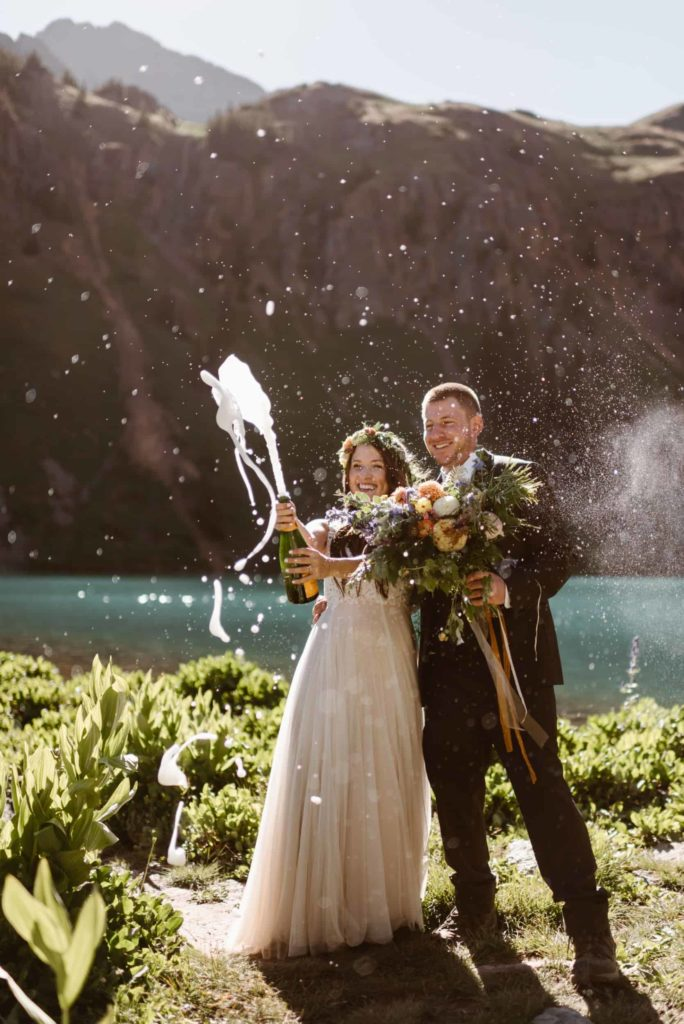 A bride pops a bottle of champagne while the groom holds her bouquet and looks on smiling.