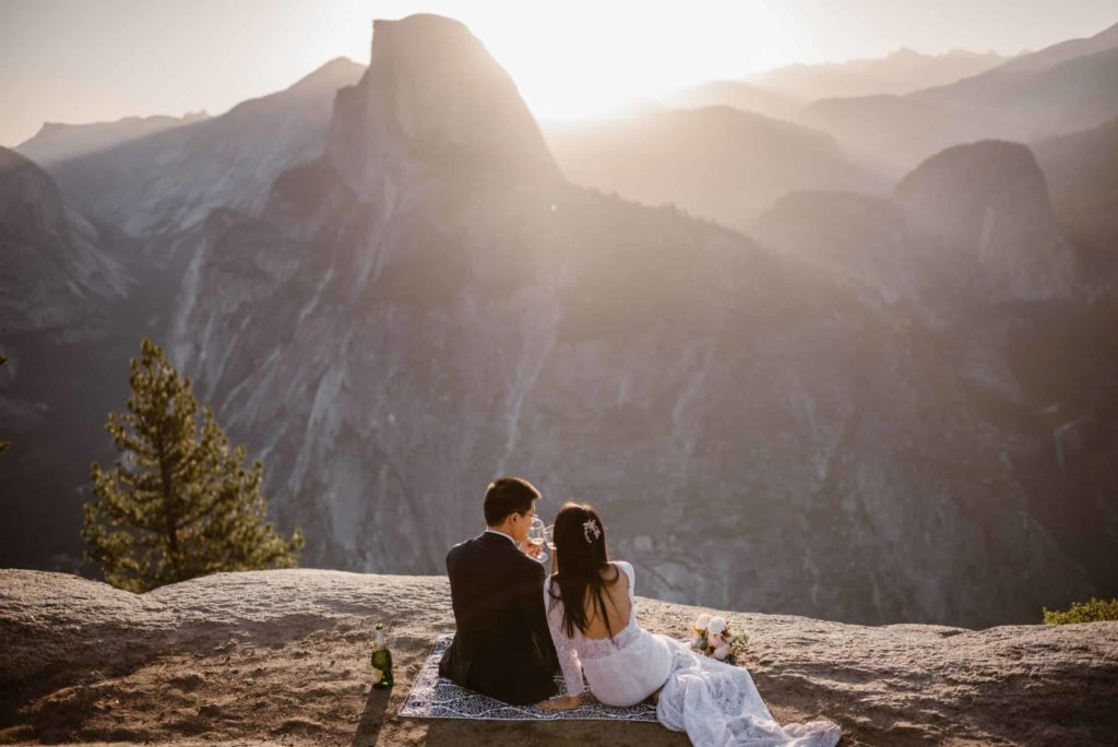 A bride and groom say a toast on the cliffs in Yosemite after their elopement.