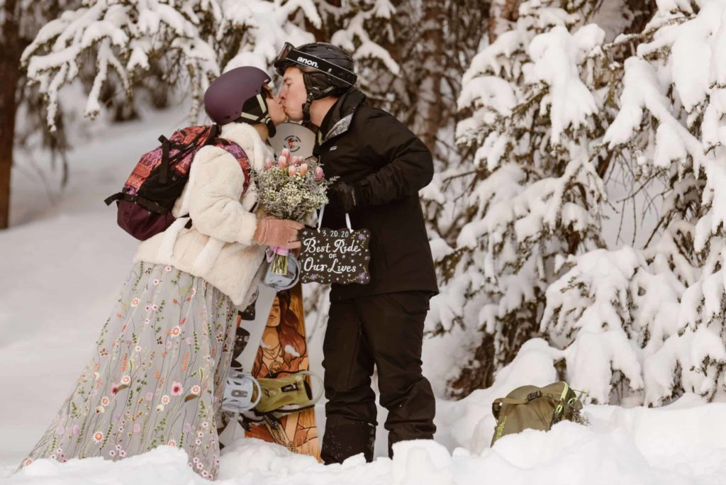 Bride and groom kiss while holding their snowboards in the snow.