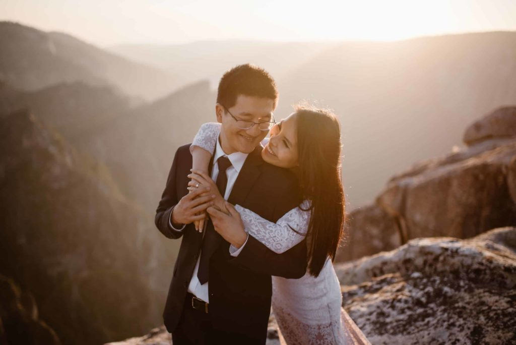 Bride and groom smile at each other while embracing on a mountain top.