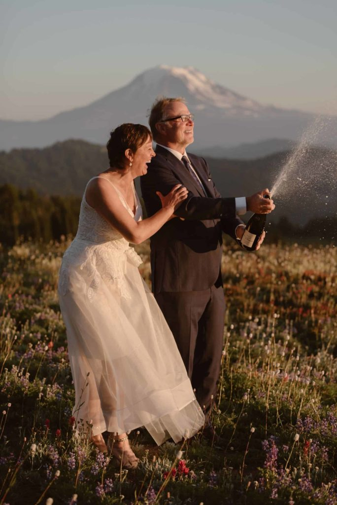 An older couple are celebrating their elopement in Oregon and popping a bottle of champagne.