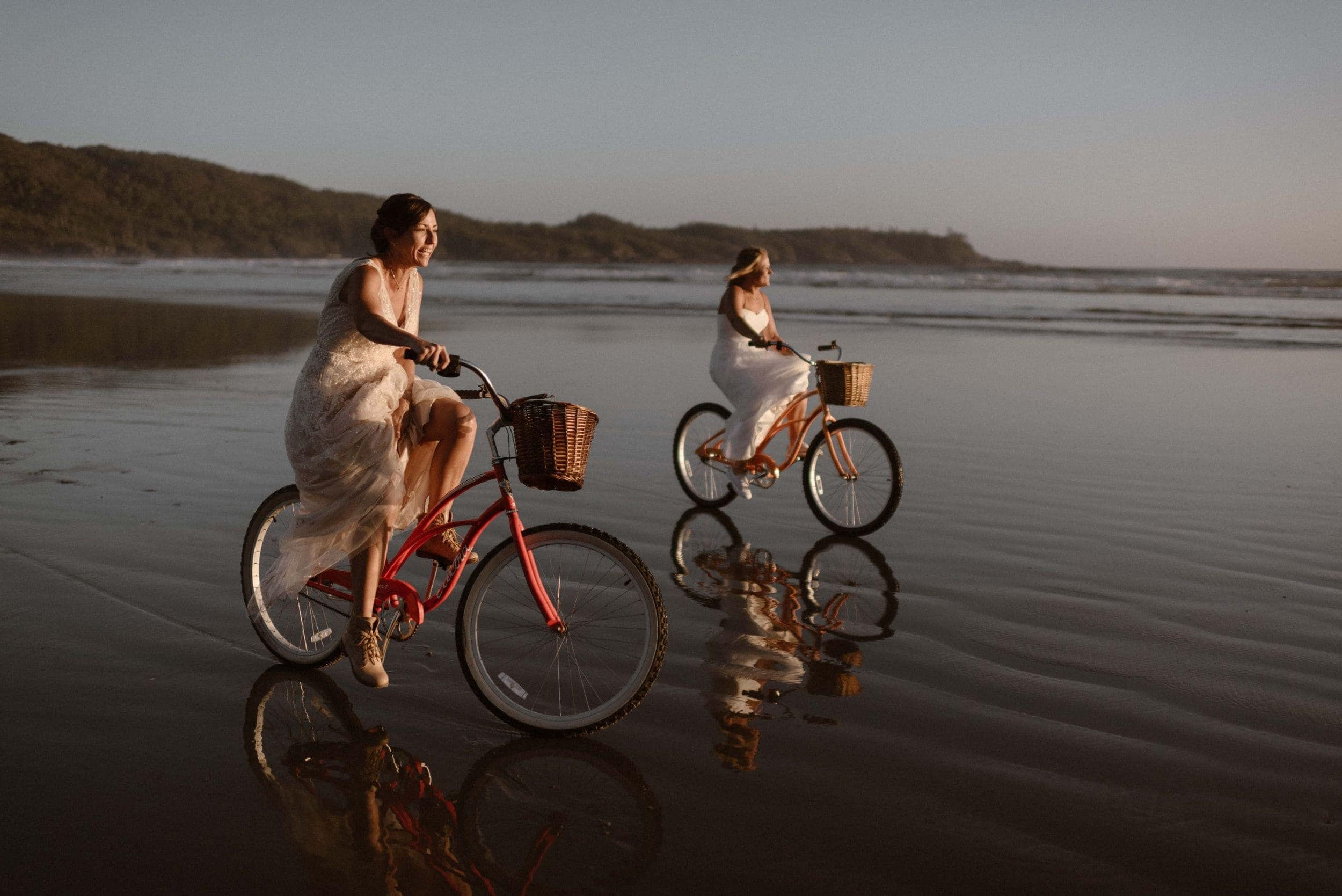 Two brides smile while riding bikes on the beach at sunset.