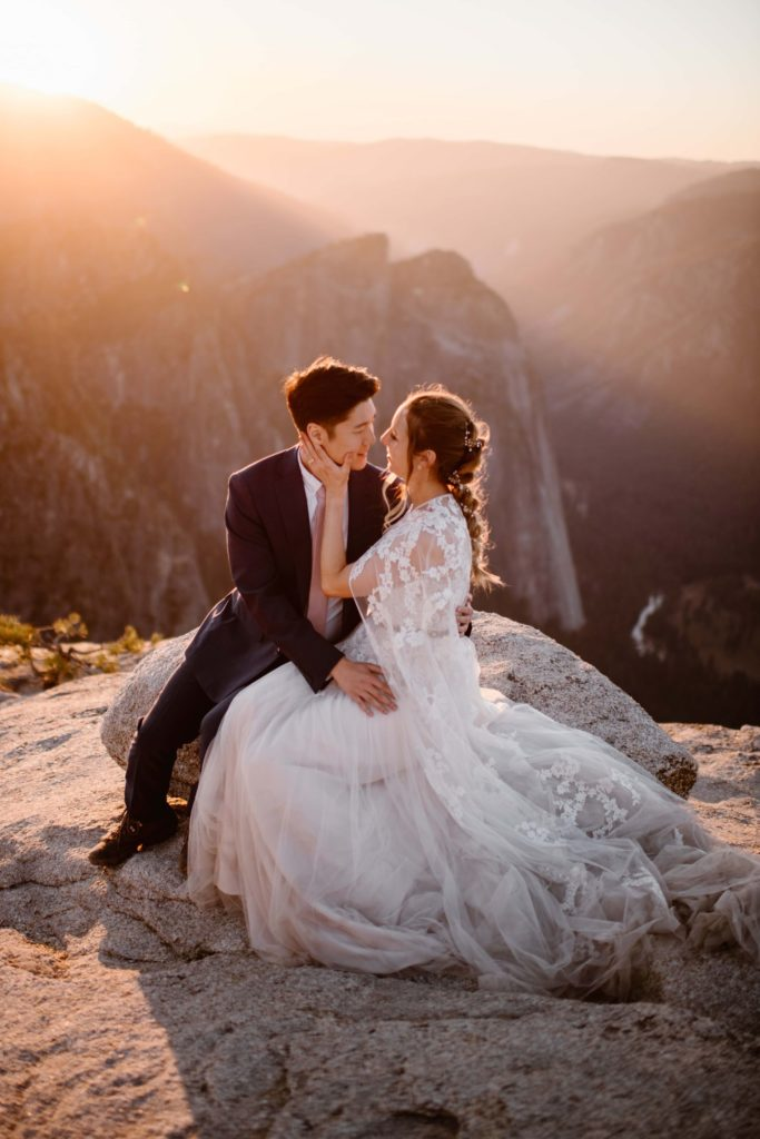 Bride and groom sit on a rock while the sun sets.