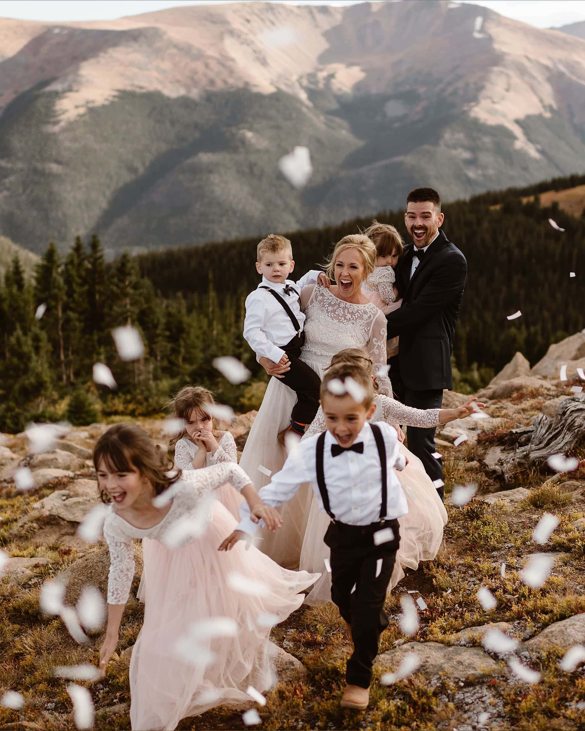A bride and groom smile at their children as they run toward confetti popping in the sky.