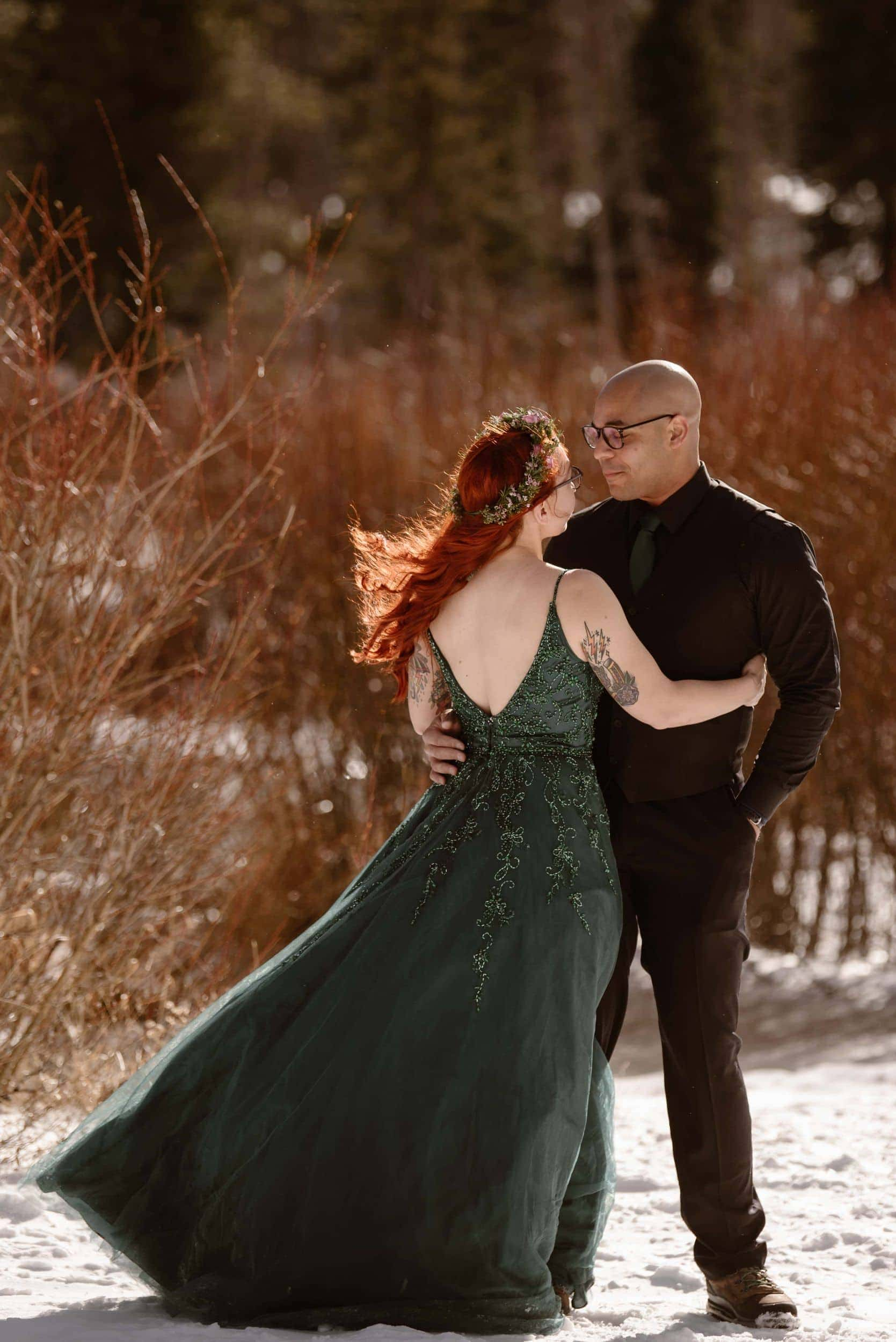 A bride and groom look at each other while standing in snow. The bride is wearing a green dress with a flower crown.