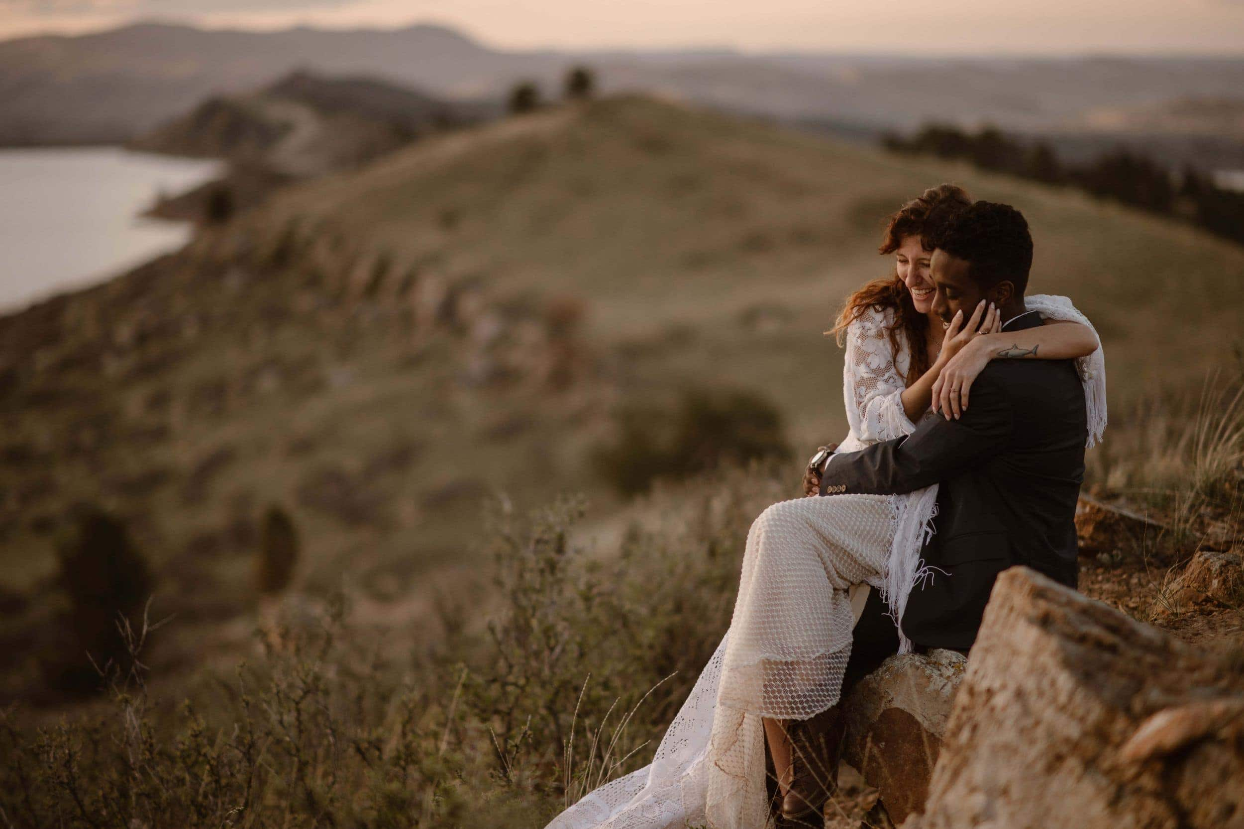 A groom holds his bride in a landscape of mountains, lakes, and meadows.