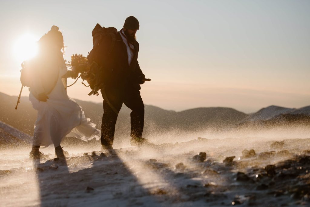 A bride and groom walk through snow as the sun sets.
