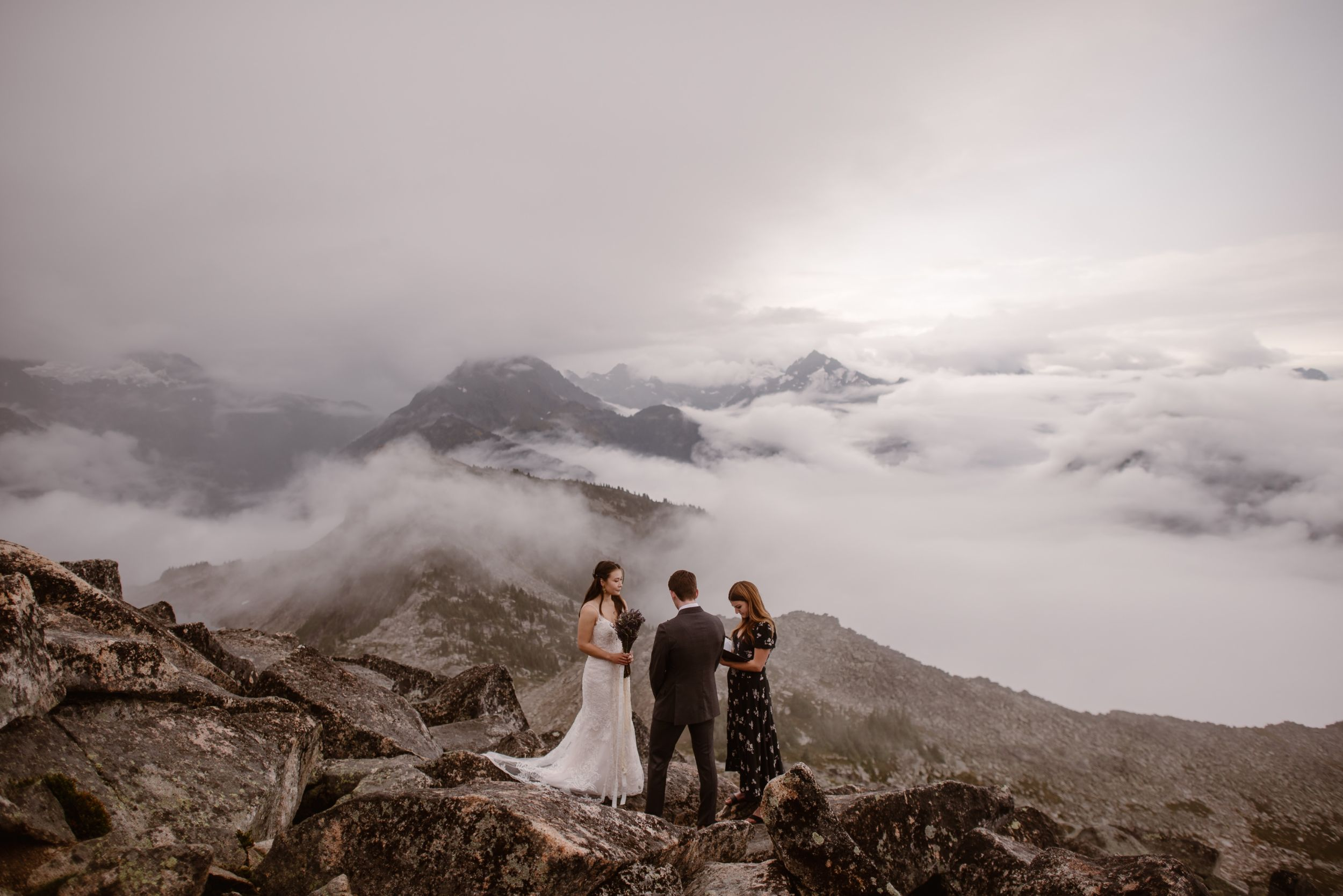 A bride and groom have a wedding ceremony with their officiant by their side. They are surrounded by cloud inversions.