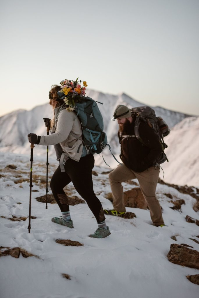 A man and woman hike up the snowy mountains. There is a bouquet of flowers in the woman's backpack.