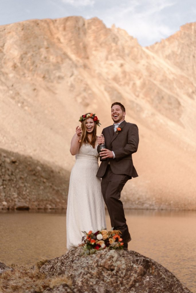 A bride and groom smile as they drink champagne near the water. The bride is wearing a flower crown and has a bouquet of flowers on the ground beside her.