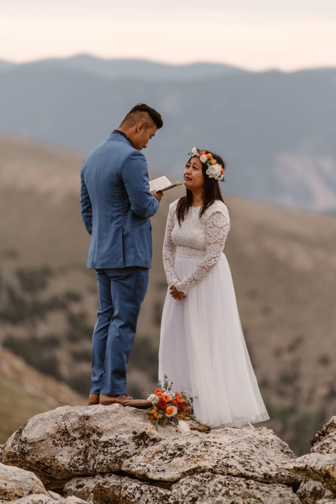 A bride and groom read vows during their elopement ceremony. The bride is wearing a flower crown and has a bouquet of flowers on the ground beside her.
