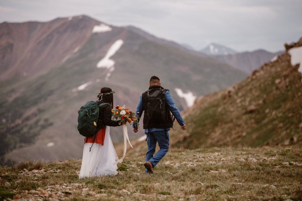 A bride and groom hike up the mountains. The bride is holding a bouquet of flowers.
