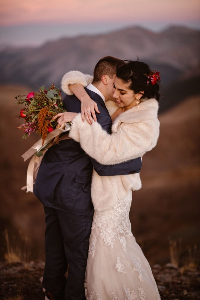 A bride and groom embrace on their wedding day. The bride has a red flower in her hair and is holding a bouquet of flowers.